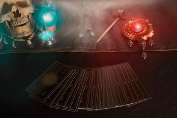Tarot card / Tarot card, skull and crystal ball on the table with smoke under candlelight. Dark tone.