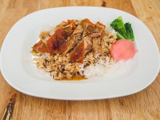 Thai rice with roasted duck in white plastic dish served on wooden table.