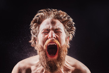 A bearded man shouts in a spray of water against a black background.