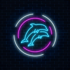 Glowing neon sign of two jumping dolphins in circle frames on dark brick wall background.