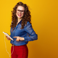 happy woman in headphones isolated on yellow using tablet PC