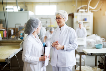 Two young joyful female workers in wearing sterile cloths are discussing statistics of food industry production while one is holding paper sheets.