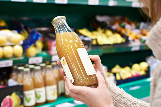 Hands with bottle of fresh apple juice in store