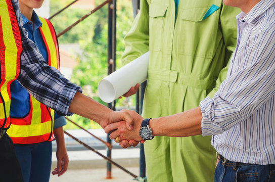 Deal, close up shaking hands of contractor, engineer and technician after finishing up business meeting to greeting start up project contract in construction site, partnership and teamwork concept