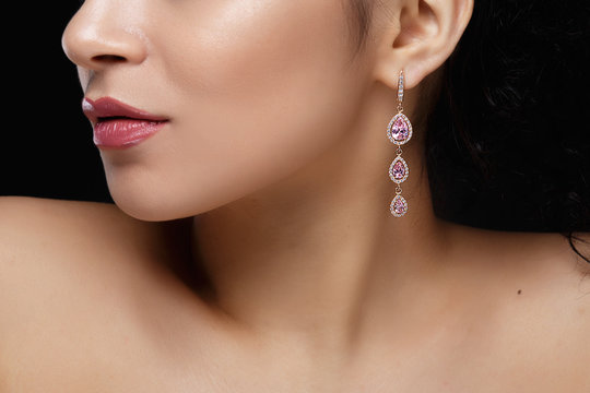 Long earring with violet precious stones hang from woman's ear