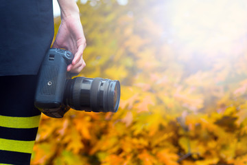 professional camera in girl's hand. Photographer on a background of bright autumn landscape