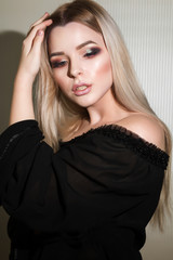 Adorable blonde woman with perfect makeup posing at the white wall