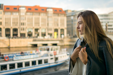 Beautiful young woman wearing coat looking away while standing near Spree river in Berlin, Germany.