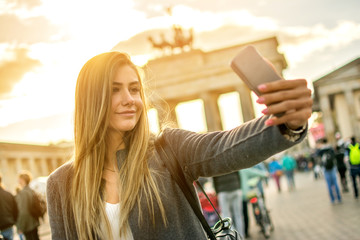 Beautiful blonde hair girl photographing with phone in Berlin city center.