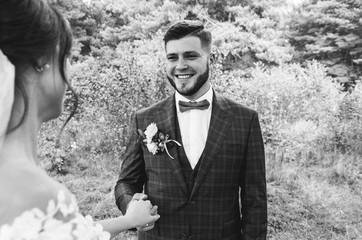 Beautiful wedding couple in the forest. Handsome bearded groom with bow tie and checkered suit in Great Gatsby style is smiling to the bride. Stylish and rustic outdoors love story. Black and white