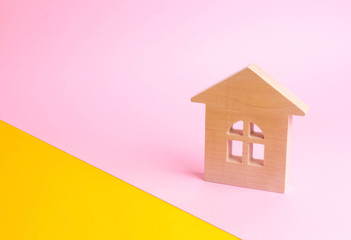 A wooden house on a pink background in pop style. The concept of renting, selling and buying a home. Juicy colors and fresh colors. Real estate market, realtors. Affordable youth housing.