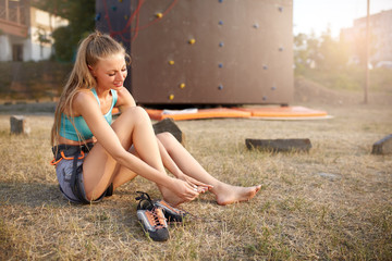 Young pretty woman having a trauma with foot after climbing practice on rock wall. Upset female climber rubbed her feetand has leg pain after training in tight climbing shoes.
