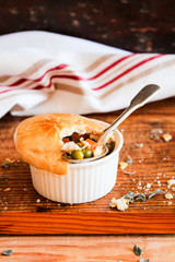 Chicken pot pies with carrot and green peas on a wooden table. Easter food. Rustic style. Comfort food. Traditional american food for lunch, dinner or summer picnic.
