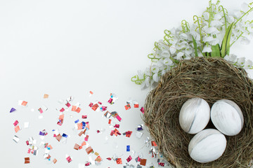 Happy Easter. Top view nest with Painted eggs on white table. Copy space for text.