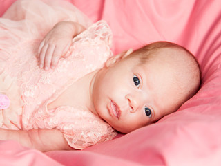 Newborn baby girl in pink dress lies on pink bed