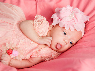 Newborn baby girl in pink dress lies on pink bed and shows tongue