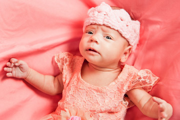 Newborn baby girl in pink dress and crochet crown, lies on pink bed.