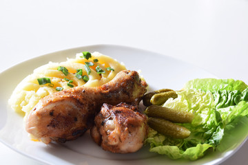 chicken drumsticks fried in a pan with potato puree with chives and fresh salad with mini cucumbers with an empty place for text