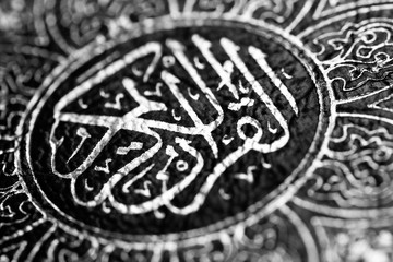 Black and white image of Islamic Book Quran with arabic calligraphy that means Al-Quran, the Holy Quran
