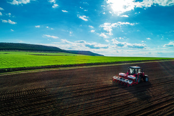 Wall Mural - Aerial view of tractors working on the harvest field