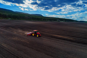 Wall Mural - Aerial view of red tractor preparing field