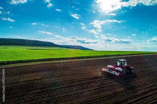 Wall mural Aerial view of tractors working on the harvest field