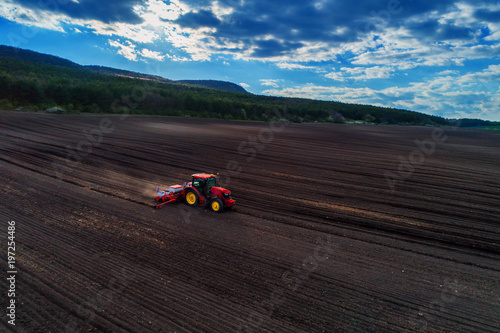 Wall mural Aerial view of red tractor preparing field
