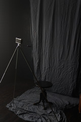 The old camera on a tripod stands in the room