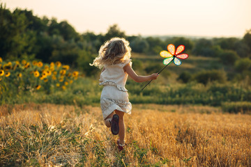 Cute little girl playing in the summer field of wheat
