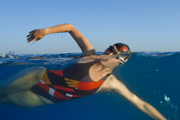 Female professional swimmer in blue water of sea in half-water split shot