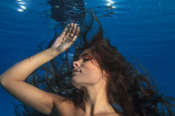 Fashion brunette model with long hair underwater on blue background