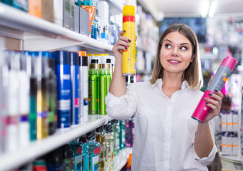 smiling young woman choosing haircare products at store