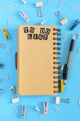 In the center lies an open notebook on springs with brown pages. Stationery in disorder on a blue background. The inscription To Do List. Mock up.