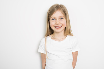 Happy small five years old girl with straight hair over white background at home