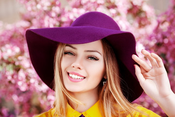 Outdoor close up portrait of young beautiful happy smiling girl posing in street with blooming trees, wearing stylish wide-brimmed violet hat, yellow shirt. Female spring fashion concept