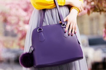 Close up photo of trendy violet bag with fur trinket in hands of fashionable woman posing in street with blooming  spring trees. Fashion elements