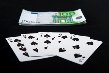 Pack of one hundred euro banknotes money on casino poker with straight flush cards on black background