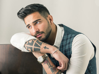 Trendy young man in studio shot wearing elegant vest and white shirt, looking away to a side