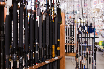Image of stand with various fishing rods in the sports shop