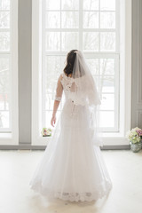 bride is staying near the window in wedding dress and veil closeup