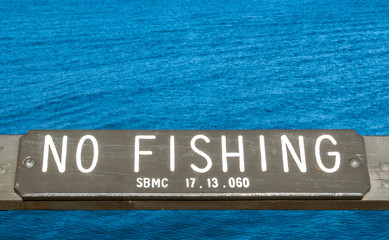 brown wooden 'No Fishing' sign on a pier at the Pacific ocean in Santa Barbara, California