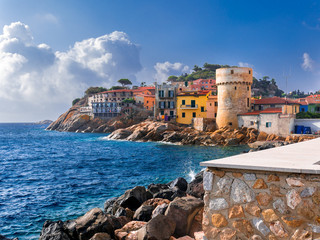 "Perfect tiny seaside village of ""Giglio Porto"" with multi colored houses, an ancient defensive tower and a rocky coastline against a deep blue Mediterranean sea. - Giglio Island, Tuscany, Italy"