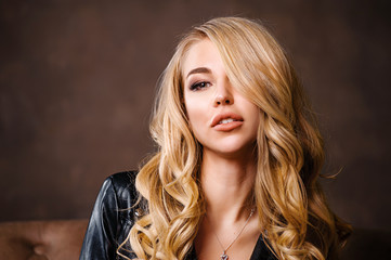 Studio portrait of a blond girl in a leather jacket