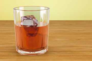 Glass with alcohol drink and ice on the wooden table. 3D rendering