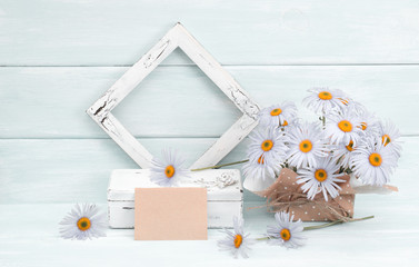 Chamomile, greeting card, casket and vintage photo frame  on wooden background in Shabby Chic style. Celebratory interior.