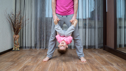 Close up photo of father and his son do acrobatic exercises. Father stands and holds the the boy's hands. Boy hangs upside down. They dressed in same color clothes.