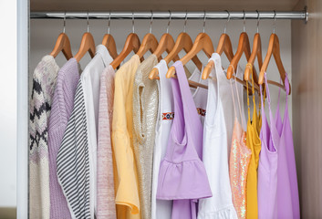 Different clothes on hangers in closet
