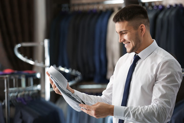 Young man choosing shirt to match his suit in boutique