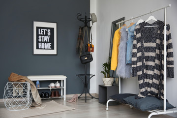 Stylish hallway interior with clothes rack and coat stand
