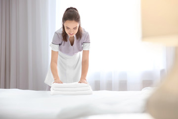 Young maid with stack of towels in hotel room